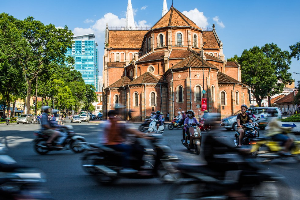Midday traffic behind Saigon Notre-Dame Cathedral