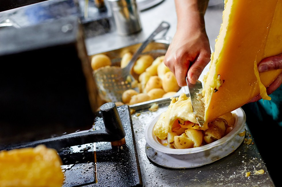 Raclette cheese melted on hot potatoes, charcuterie and vegetables