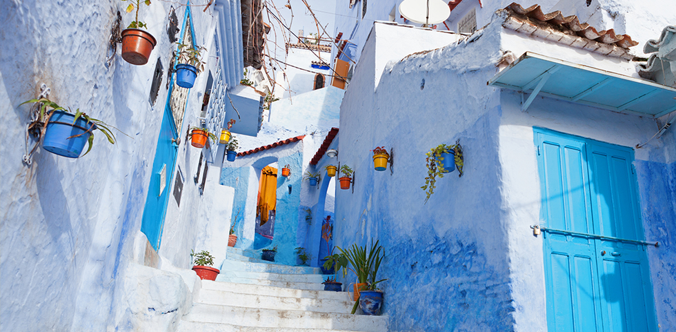 Stairwell featuring homes of various shades of blue in Chefchaouen, Morocco