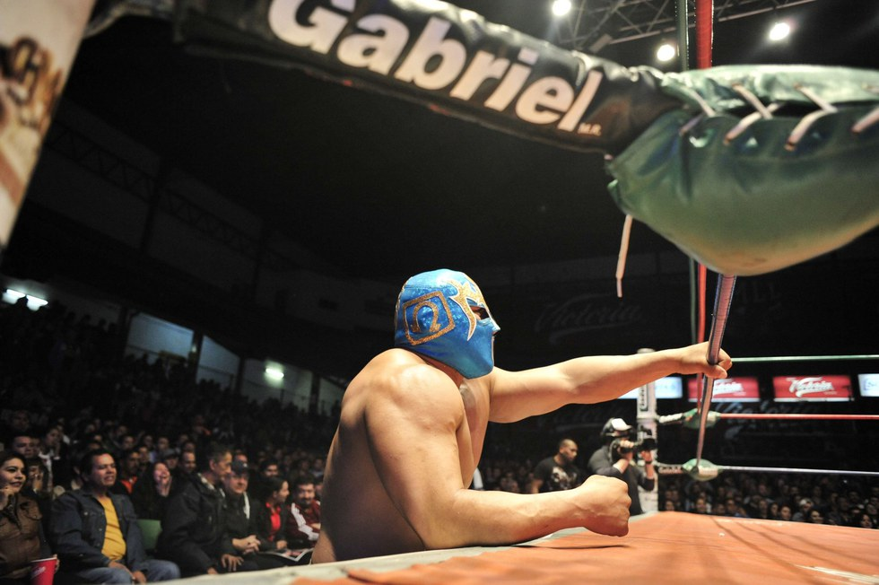 Masked wrestlers hurl each other around as a crowd watches