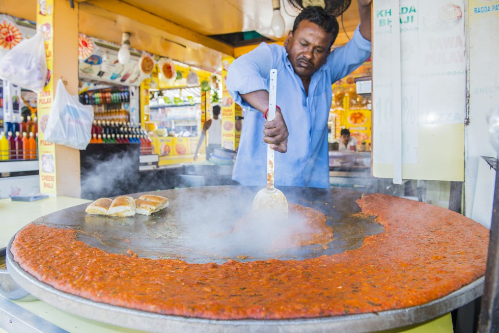 A street vendor prepares pav bhaji