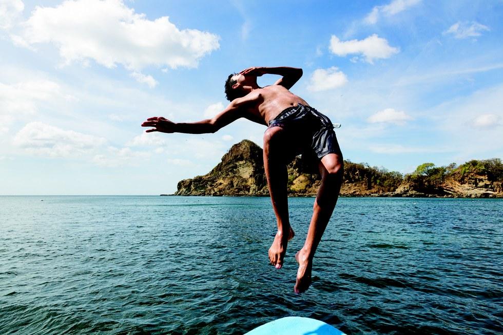 A swimmer backflips into the Bahia la Redonda