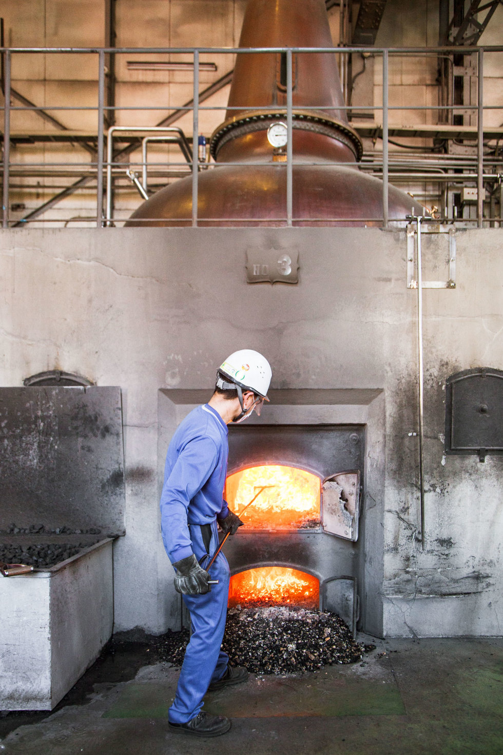 A worker shovels coal into a fire to heat a still at the Yoichi Distillery