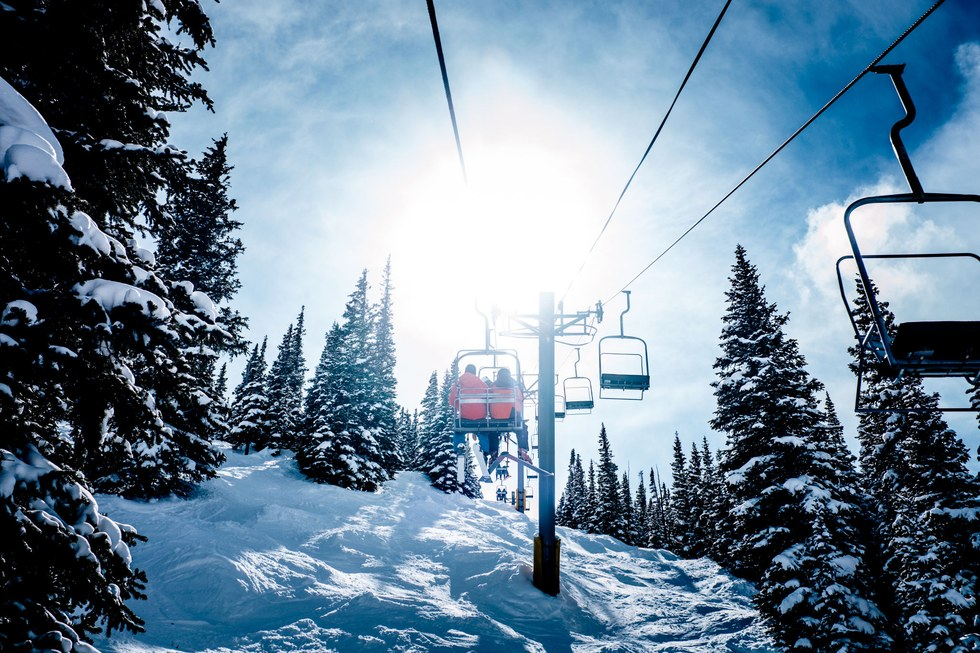Skiers ride a chairlift at snow-covered Breckenridge