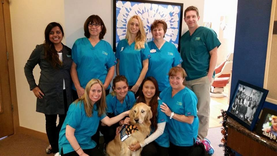 Golden retriever who works at dental clinic with staff
