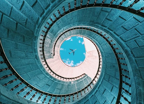 Looking up a winding staircase to a plane passing by