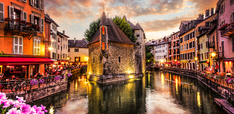 A canal in Annecy, France with cobblestone streets and homes along it.