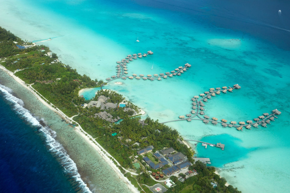 Overwater bungalows on a motu, seen from a Tahiti Air Charter seaplane