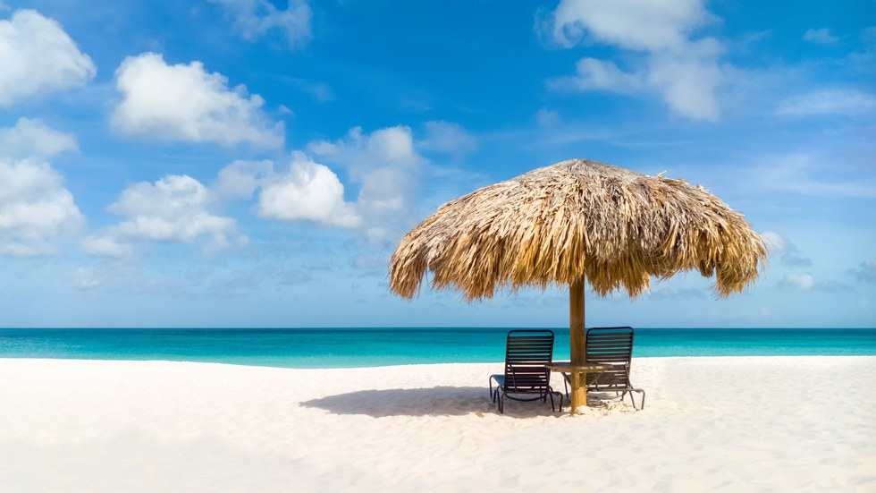 Two chairs and an umbrella on the beach in Aruba