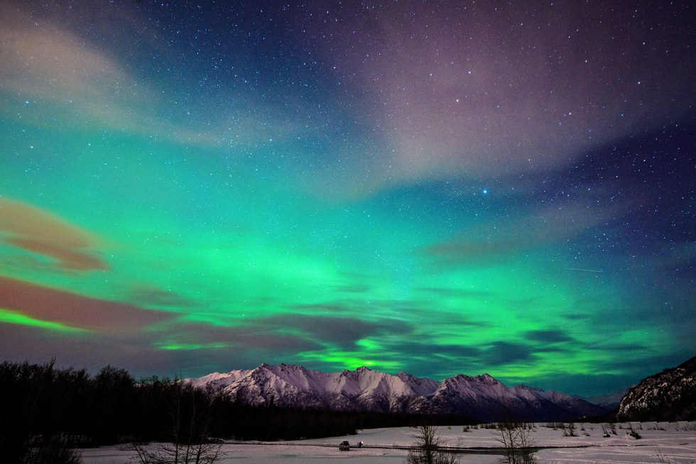 Northern Lights with mountains in the distance in Alaska.