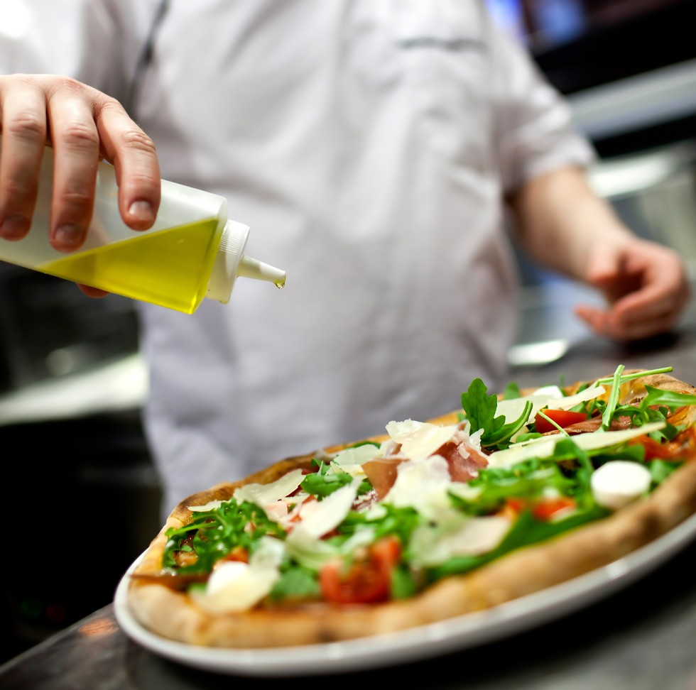 olive oil being drizzled on a pizza