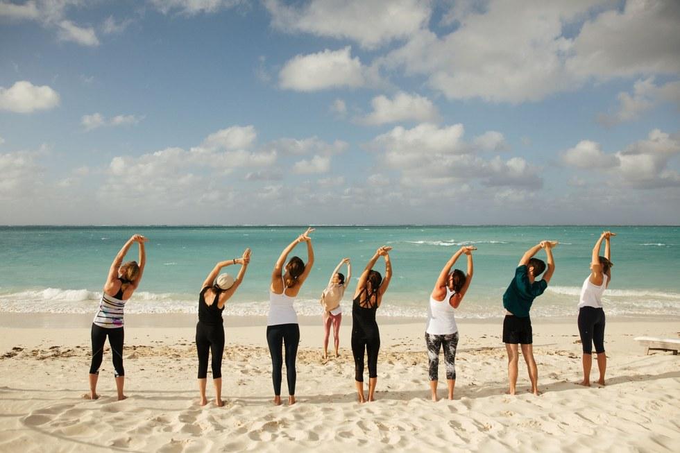 A yoga instructor leads a yoga class on the beach