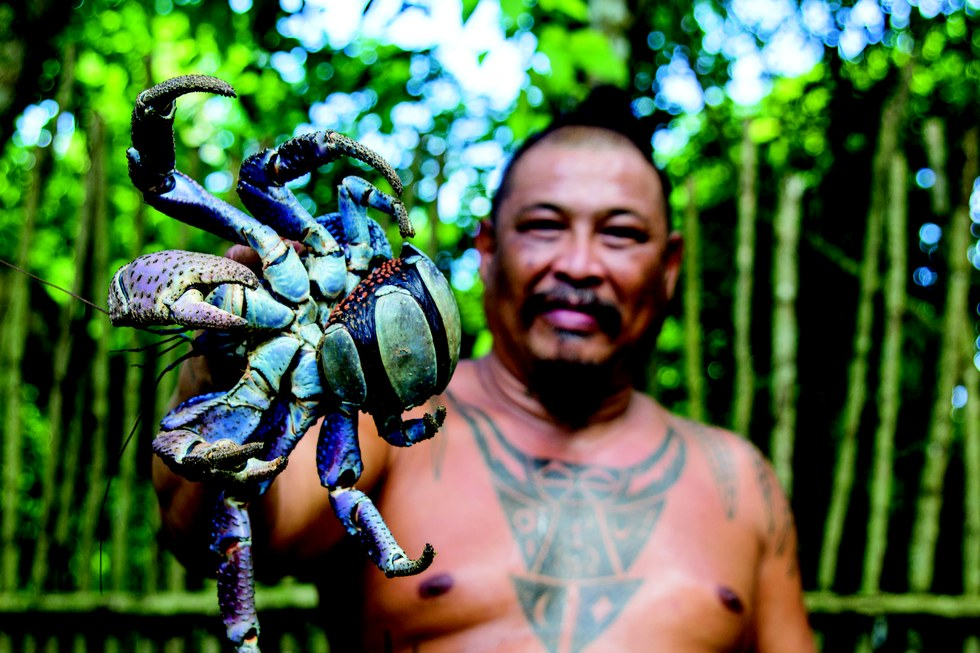 A local holds a coconut crab in Lina'la' Park