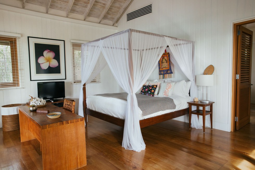One of Como Parrot Cay's rooms, which all feature four-post beds