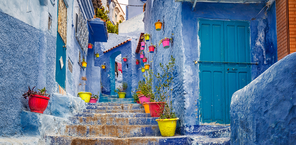 Blue walk stairwell with colorful pots in Morocco
