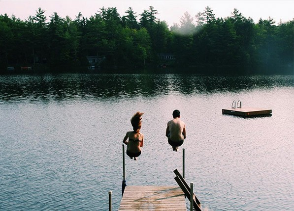 Two people cannon balling into a lake