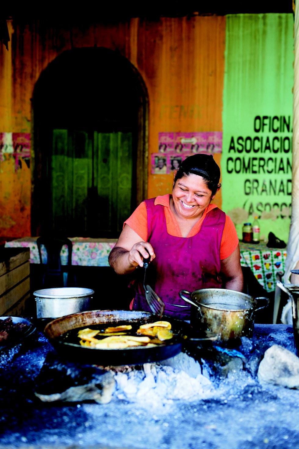 A woman fries plantains at Granada's Mercado Municipal