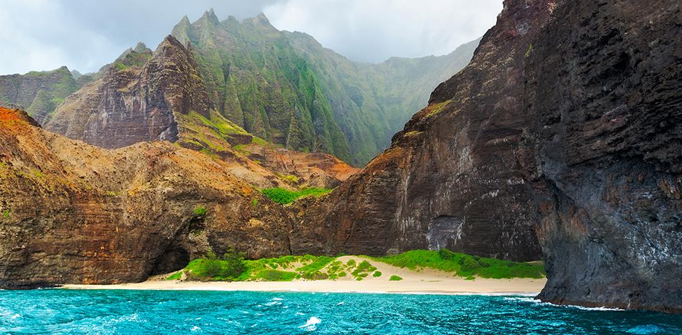 Hidden beach below emerald green cliffs in Kauai, Hawaii