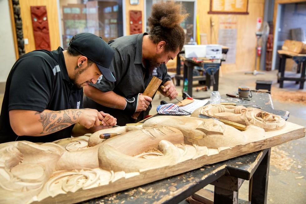 Two men carving at The Maori carving school at Te Puia