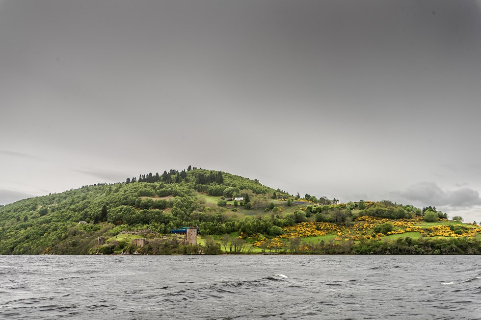 View of ruins of a castle from a boat in Loch Ness.